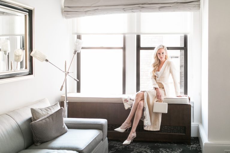 She sits dressed in white by the window, her blonde hair blending in with her luxury robe and designer heels.