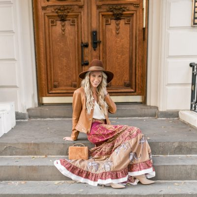 Woman in bohemian outfit sitting on steps.