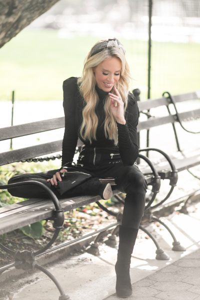 Blonde woman on park bench looking down while smiling.
